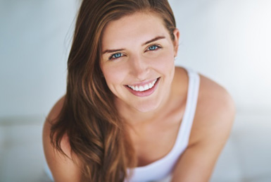 Young woman wearing white tank top looking up at camera and smiling after a whitening treatment in Princeton, NJ